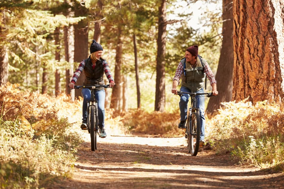 man and woman riding mountain bike on forest trail