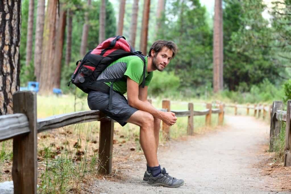 man wearing backpack resting on railing in park