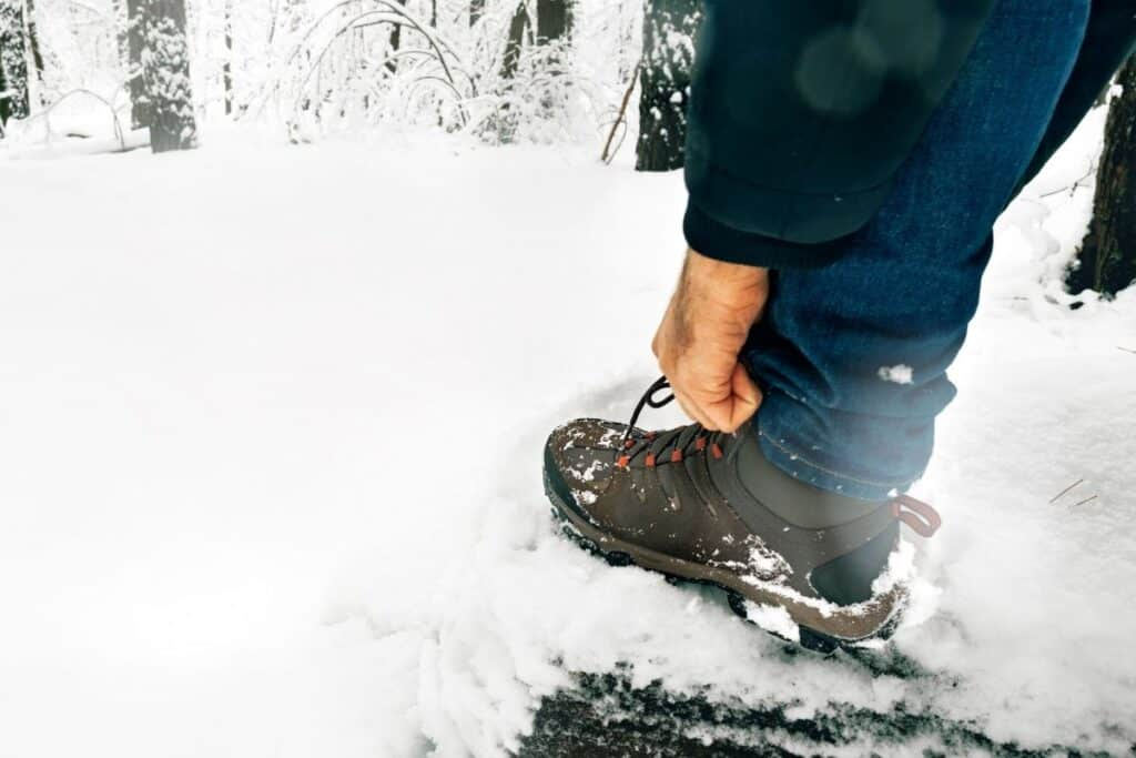 Many tying hiking shoe laces in snowy forest