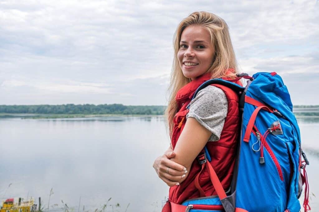 woman wearing hiking backpack by water