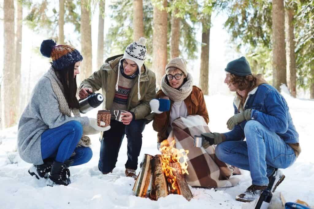 friends around campfire in snowy forest