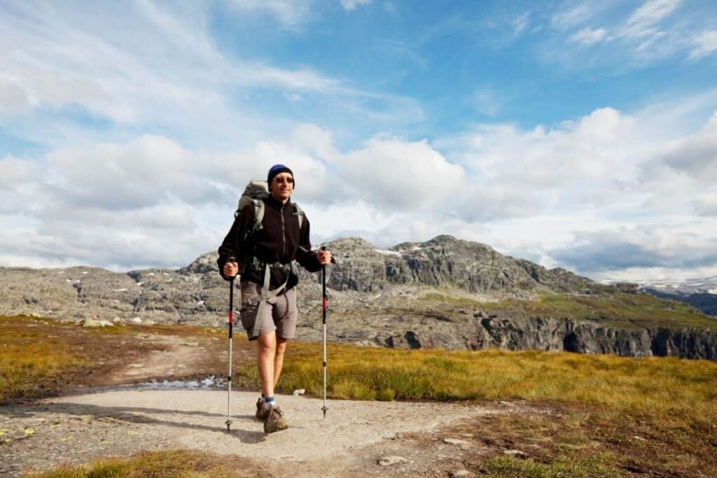man hiking with trekking poles