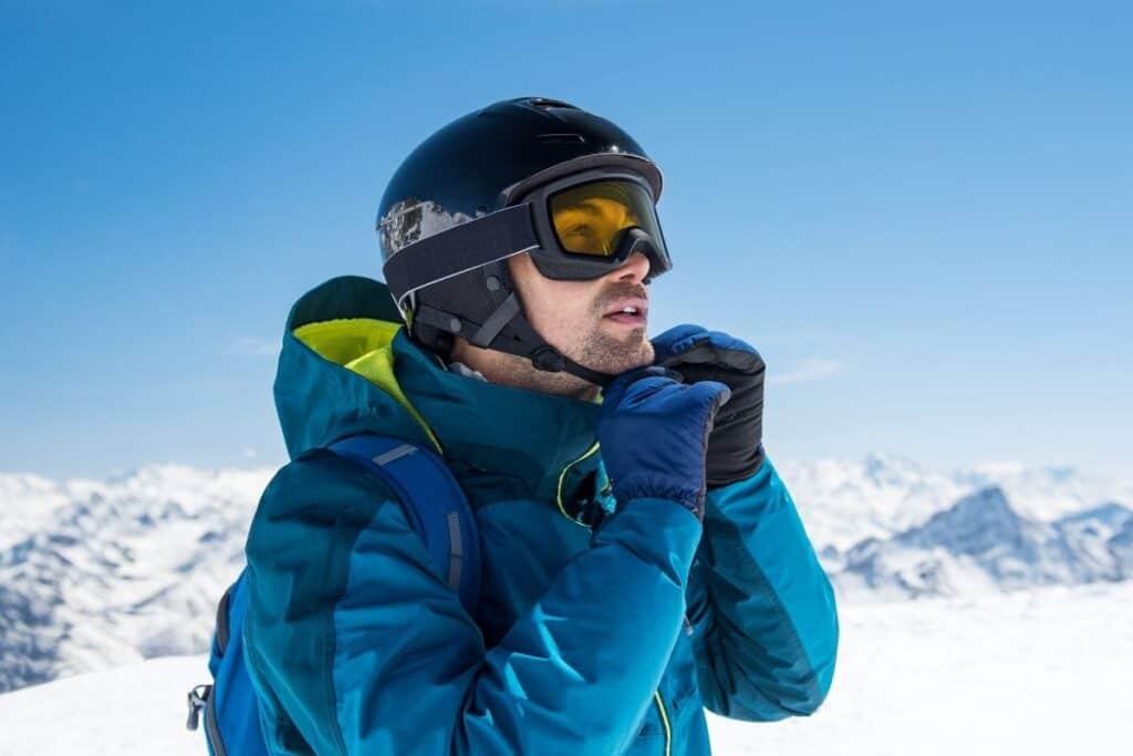 man attaching chin strap on ski helmet