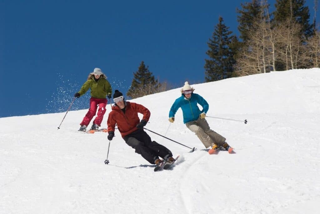 group of three skiers going downhilll