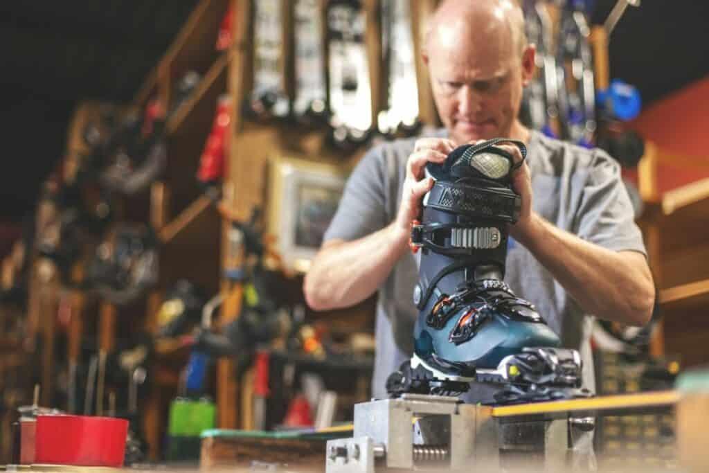 man adjusting ski binding in shop