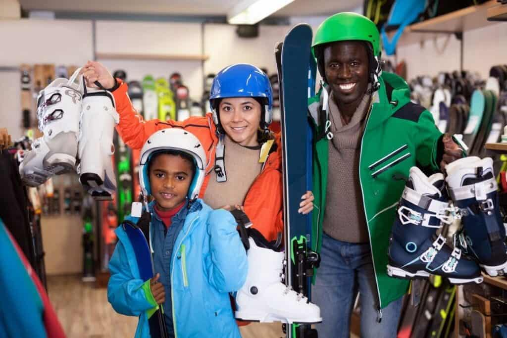 man, woman, and child holding up ski boots